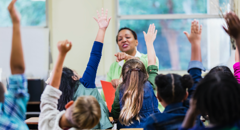Image of teacher addressing class selecting a student with a raised hand